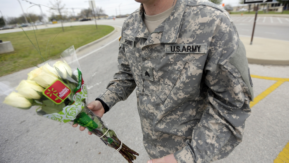 An unidentified soldier holds flowers dropped off at Fort Hood's main gate for shooting victims, Thursday, April 3, 2014, in Fort Hood, Texas. (AP Photo/Eric Gay)