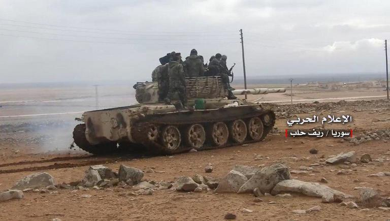 This photo provided on Saturday, Jan. 20, 2018, by the government-controlled Syrian Central Military Media, shows Syrian government forces standing on their tank, in the southern Aleppo countryside, Syria. Syrian state TV says government forces have retaken a key air base in northwest Syria that was lost to rebels in 2015. The state broadcaster says Syrian troops fought their way into the strategic Abu Zuhour air base on Saturday, in Idlib province. (Syrian Central Military Media, via AP)
