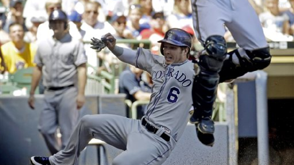 Colorado Rockies' Corey Dickerson (6) scores as Milwaukee Brewers catcher Jonathan Lucroy leaps for a throw during the fifth inning of a baseball game Sunday, June 29, 2014, in Milwaukee. (AP Photo/Morry Gash)