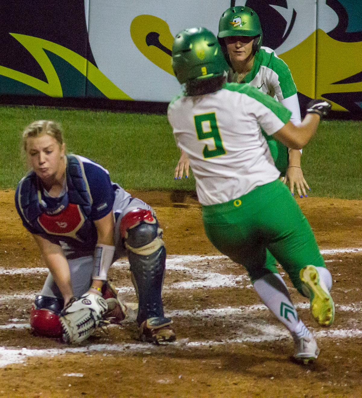Ducks center-fielder Shannon Rhodes (#9) scores as a teammate looks on. The No. 3 Oregon Ducks defeated the University of Illinois Chicago Flames 13-0 with the run-rule on Saturday night at Jane Sanders Stadium. The Ducks scored in every inning and then scored nine runs at the bottom of the fourth. The Oregon Ducks are now 22-0 in NCAA regional games. The Oregon Ducks play Wisconsin next on Saturday, May 20 at 2pm at Jane Sanders Stadium. Photo by Aaron Alter, Oregon News Lab