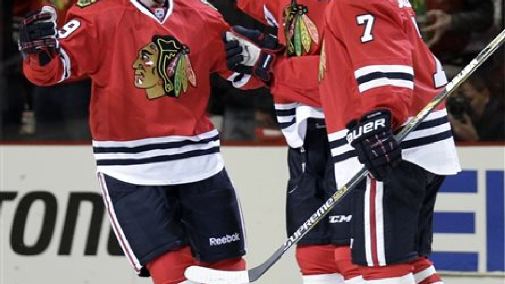 Chicago Blackhawks' Bryan Bickell, left, celebrates with teammate Marian Hossa, center, and Brent Seabrook (7) after scoring a goal against the St. Louis Blues during the first period in Game 6 of a first-round NHL hockey playoff series in Chicago, Sunday, April 27, 2014. (AP Photo/Nam Y. Huh)