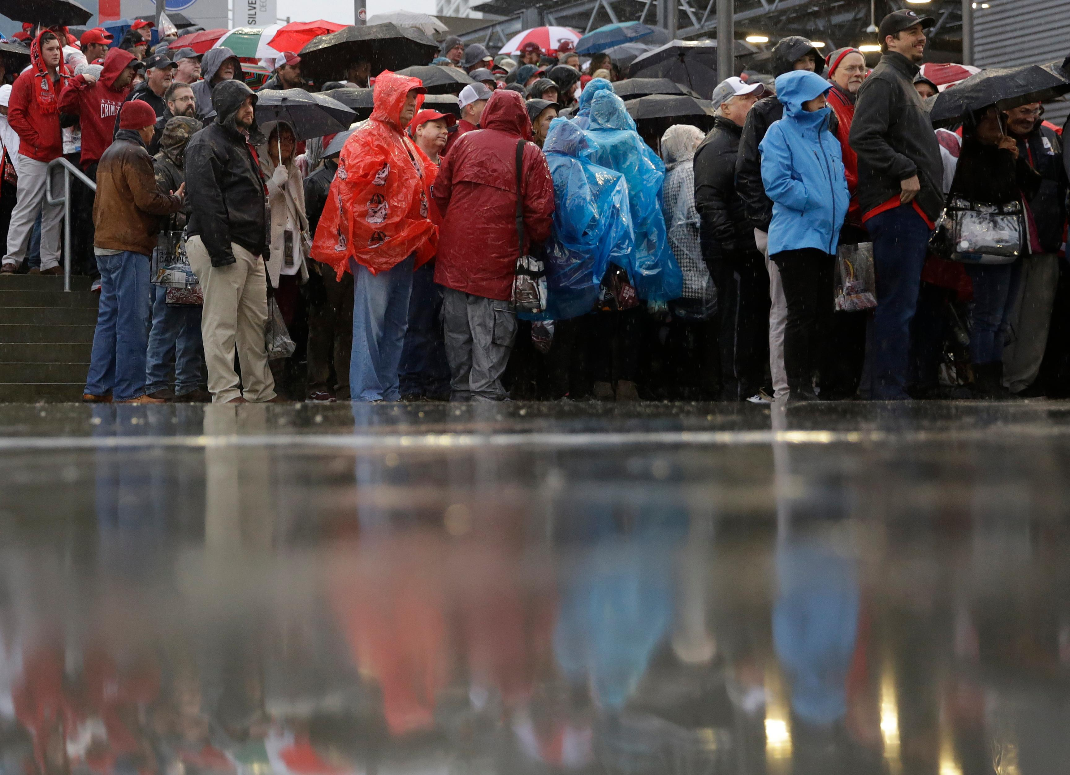 Fans wait in a line outside Mercedes-Benz Stadium before the NCAA college football playoff championship game between Georgia and Alabama Monday, Jan. 8, 2018, in Atlanta. (AP Photo/David Goldman)