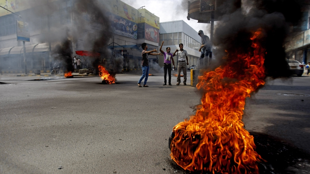 Yemenis set tires on fire during a protest against the inflation of fuel prices in Sanaa, Yemen, Wednesday, July 30, 2014. Yemeni protesters blocked roads by burning tires on streets in the Yemeni capital against the government's decision to raise fuel prices. The fuel crisis which hit the country for the past several months has lead to many gas stations shutting down and cars queuing for miles at stations that still sell fuel. The crisis affected public transportation drivers mostly. (AP Photo/Hani Mohammed)
