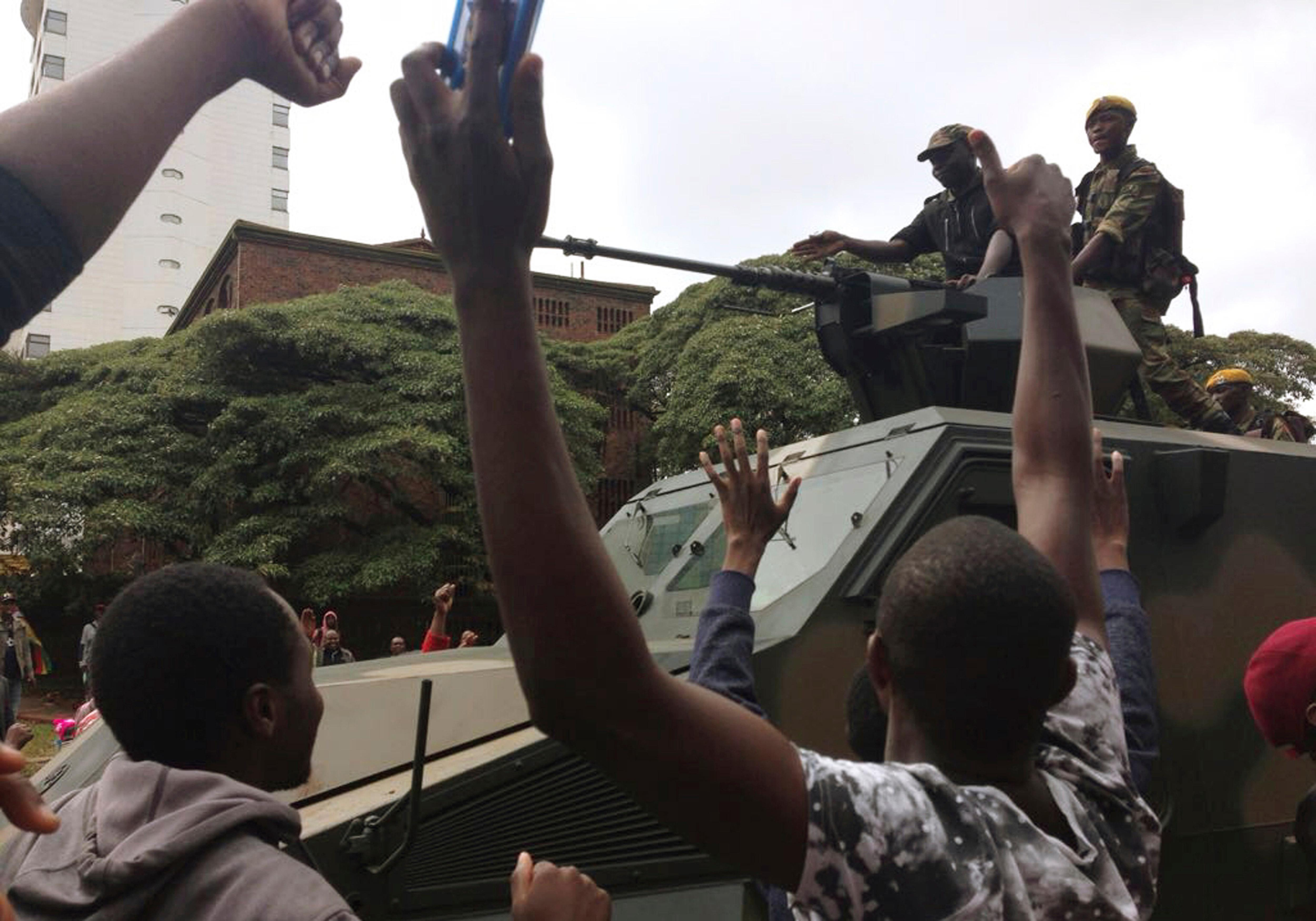 People begin to gather around a military vehicle in Harare Saturday, Nov. 18, 2017, demonstrating for the ouster of 93-year-old president Robert Mugabe who is virtually powerless and deserted by most of his allies. Zimbabwe's generals, have placed Mugabe under house arrest and have allowed him limited movement while talks on his exit from office unfold. (AP Photo/Christopher Torchia)