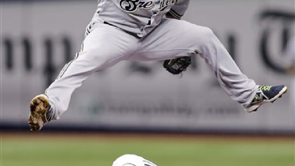 Milwaukee Brewers shortstop Jean Segura leaps over Tampa Bay Rays' Curt Casali after forcing him at second base on a fielder's choice by Kevin Kiermaier during the third inning of a baseball game Tuesday, July 29, 2014, in St. Petersburg, Fla. (AP Photo/Chris O'Meara)