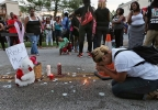 Meghan O'Donnell, 29, from St. Louis, prays at the spot where Michael Brown was killed the previous afternoon, Sunday evening, Aug. 10, 2014, in Ferguson, Mo. Police said Brown, who was unarmed, was fatally shot Saturday in a scuffle with an officer. (AP Photo/St. Louis Post-Dispatch, J.B. Forbes)