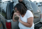 Lucy Hamlin and her husband, Spc. Timothy Hamlin wait for permission to re-enter the Fort Hood military base, where they live, following a shooting on base on Wednesday, April 2, 2014, in Fort Hood, Texas. (AP Photo/Tamir Kalifa)