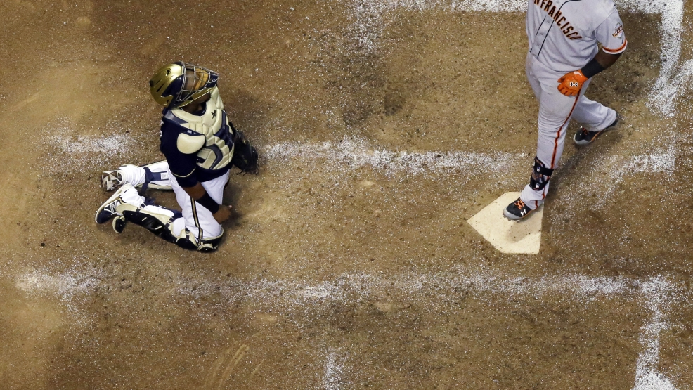 Milwaukee Brewers catcher Martin Maldonado watches as San Francisco Giants' Pablo Sandoval gestures as he steps on home plate on a two-run home run during the eighth inning of a baseball game Wednesday, Aug. 6, 2014, in Milwaukee. (AP Photo/Morry Gash)
