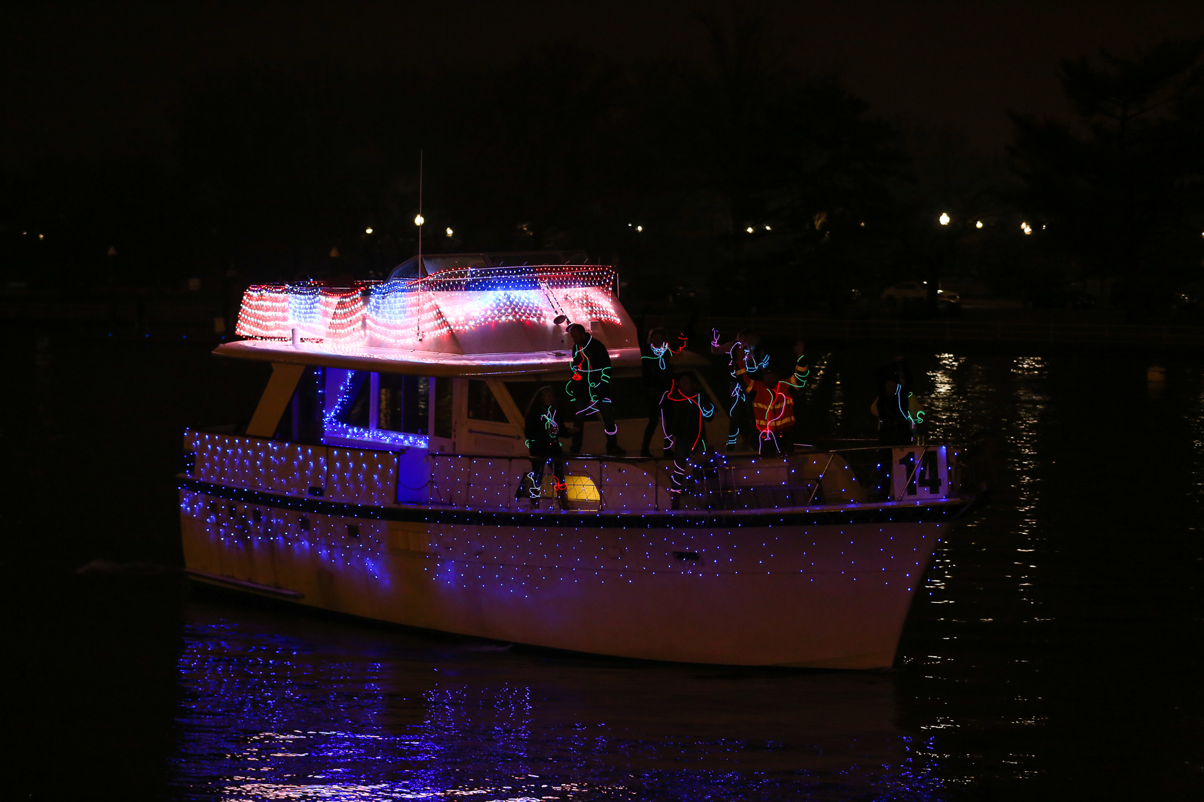 Dozens of boats decked out in glittering lights glided past The Wharf on December 1 for The District's Holiday Boat Parade. The themes ranged from 'The Nightmare Before Christmas' to a Hanukkah rave and the crowds cheered for their favorites. Guests also enjoyed photos with Santa, a live performance from Go Go Gadjet, s'mores and a fireworks display. (Amanda Andrade-Rhoades/DC Refined)<br>