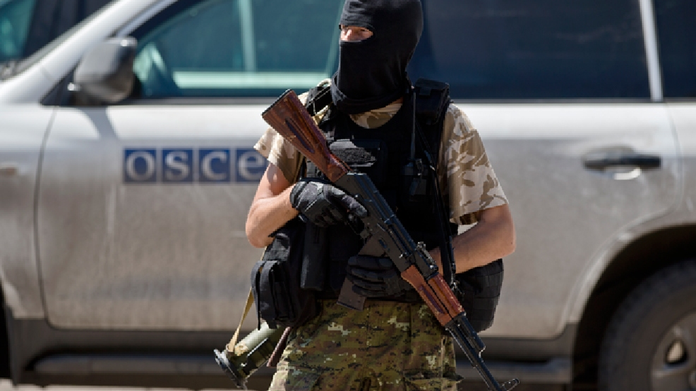 A pro-Russian rebel stands outside the railway station after members of the OSCE mission to Ukraine and Holland's National Forensic Investigations Team inspected a refrigerated train loaded with the bodies of passengers in Torez, eastern Ukraine, 15 kilometers (9 miles) from the crash site of Malaysia Airlines Flight 17, Monday, July 21, 2014. (AP Photo/Vadim Ghirda)