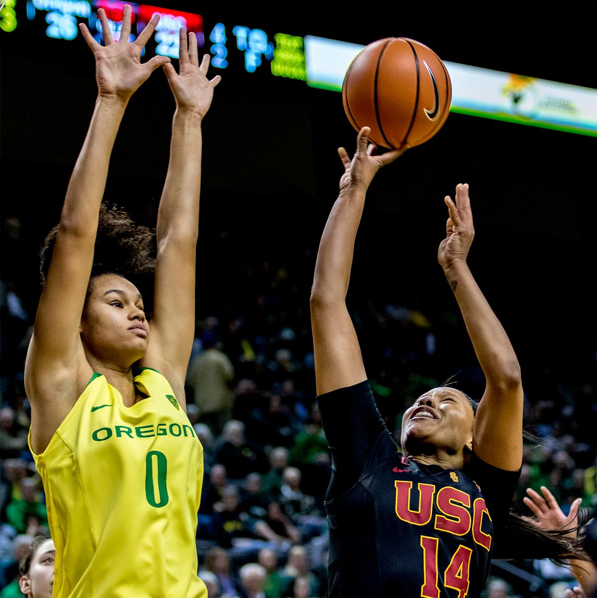 The Trojan's Sadie Edwards (#14) shoots for the basket as the Duck's Satou Sabally (#0) defends. The Oregon Ducks defeated the USC Trojans 80-74 on Friday at Matthew Knight Arena in a  game that went into double overtime. Lexi Bando sealed the Ducks victory by scoring a three-pointer in the closing of the game. Ruthy Hebard set a new NCAA record of 30 consecutive field goals, the old record being 28. Ruthy Hebard got a double-double with 27 points and 10 rebounds, Mallory McGwire also had 10 rebounds. The ducks had four players in double digits. The Ducks are now 24-4, 13-2 in the Pac-12, and are tied for first with Stanford. Photo by August Frank, Oregon News Lab