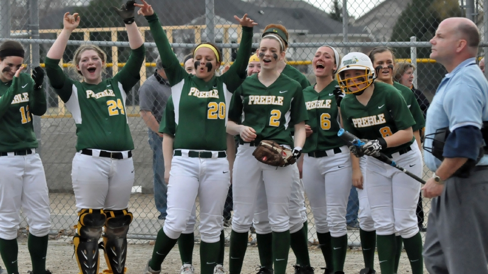 Green Bay Preble players wait at home plate as Kaylen Krueger rounds the bases after a home run against De Pere during Monday's game. (Doug Ritchay/WLUK)