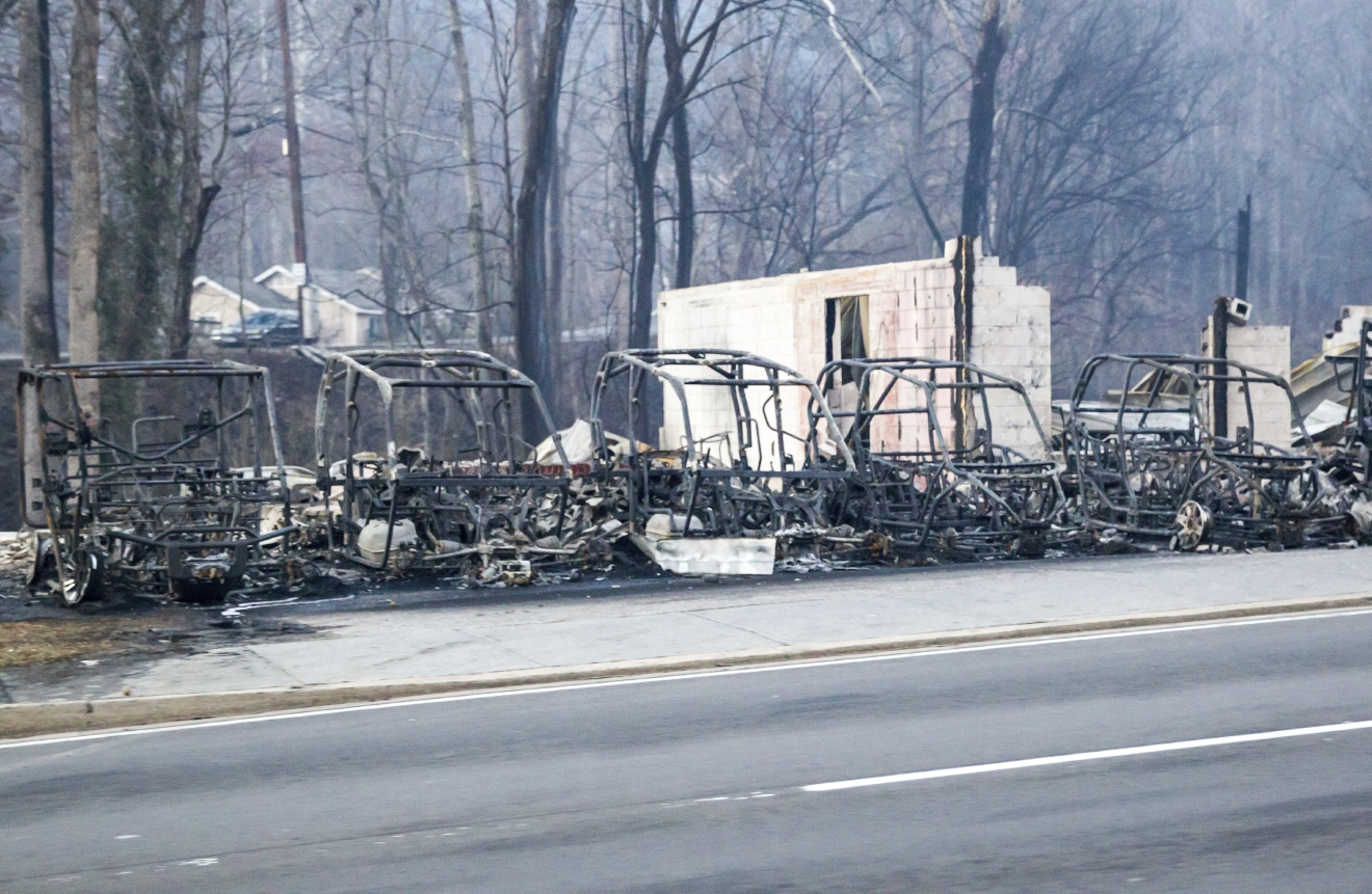 Burned out frames side-by-side utility vehicles sit at the side of the road in Gatlinburg, Tenn., Tuesday, Nov. 29, 2016. The fatal wildfires swept over the tourist town the night before, causing widespread damage. (AP Photo/Erik Schelzig)