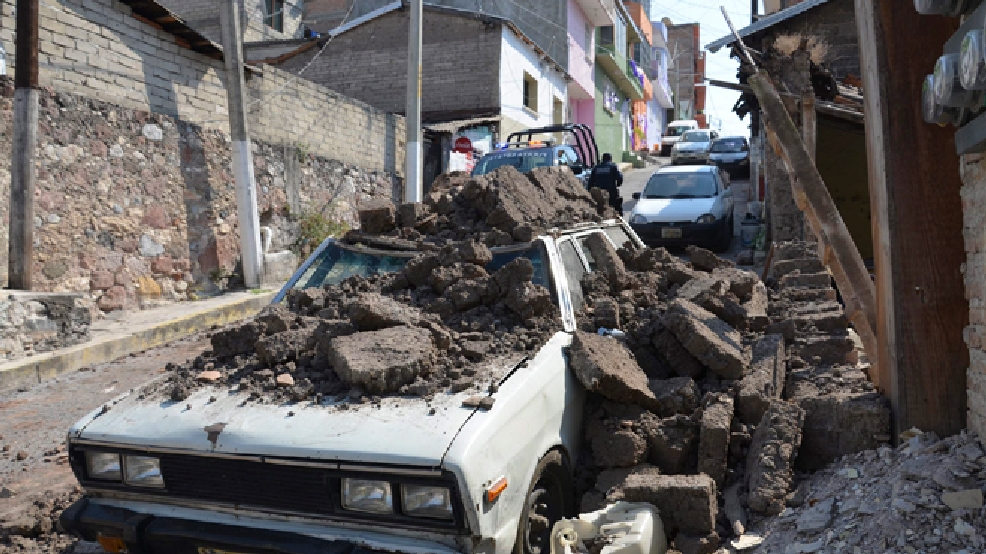 A parked car suffered damage when a adobe wall collapsed on it after a strong earthquake shook Chilpancingo, Mexico, Friday morning, April 18, 2014. A powerful magnitude-7.2 earthquake shook central and southern Mexico but there were no early reports of major damage or casualties. (AP Photo/Alejandrino Gonzalez)