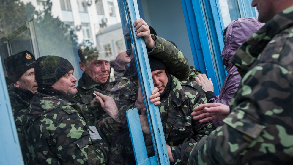 Pro-Russian self-defense force members get through an entrance to the Ukrainian Navy headquarters in Sevastopol, Crimea, Wednesday, March 19, 2014. An Associated Press photographer said several hundred militiamen took down the gate and made their way onto the base. They then raised the Russian flag in the square by the headquarters. The unarmed militia waited for an hour on the square before the move to storm the headquarters. Following the arrival of the commander of the Russian Black Sea fleet, the Crimeans took over the building. (AP Photo/Andrew Lubimov)