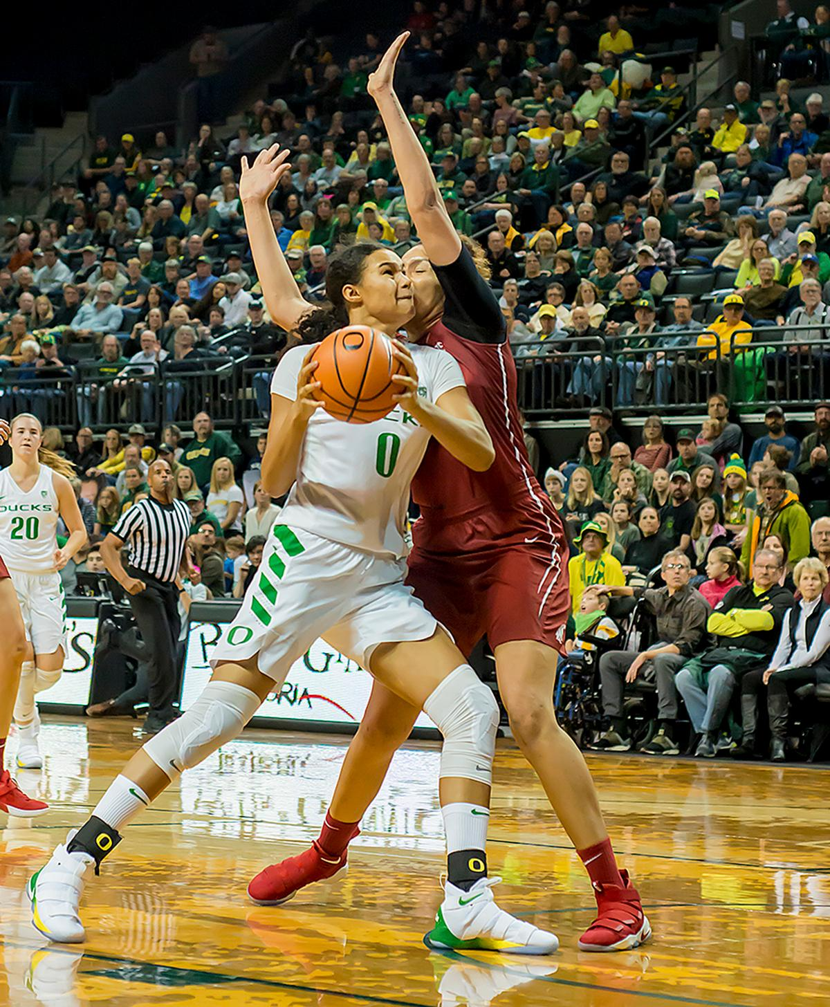 Oregon Ducks Satou Sabally (#0) attempts to drive past the block of Washington State University Cougars Nike McClure (#21). In their first conference basketball game of the season, the Oregon Women Ducks defeated the Washington State Cougars 89-56 in Matt Knight Arena Saturday afternoon. Oregon's Ruthy Hebard ran up 25 points with 10 rebounds. Sabrina Ionescu shot 25 points with five three-pointers and three rebounds. Lexi Bando added 18 points, with four three-pointers and pulled down three rebounds. Satou Sabally ended the game with 14 points with one three-pointer and two rebounds. The Ducks are now 12-2 overall with 1-0 in conference and the Cougars stand at 7-6 overall and 0-1 in conference play. The Oregon Women Ducks next play the University of Washington Huskies at 1:00 pm on Sunday. Photo by Karly DeWees, Oregon News Lab