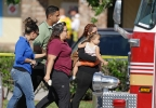 Parents and relatives leave a day care center with their children after a vehicle crashed into the center, Wednesday, April 9, 2014, in Winter Park, Fla. (AP Photo/John Raoux)