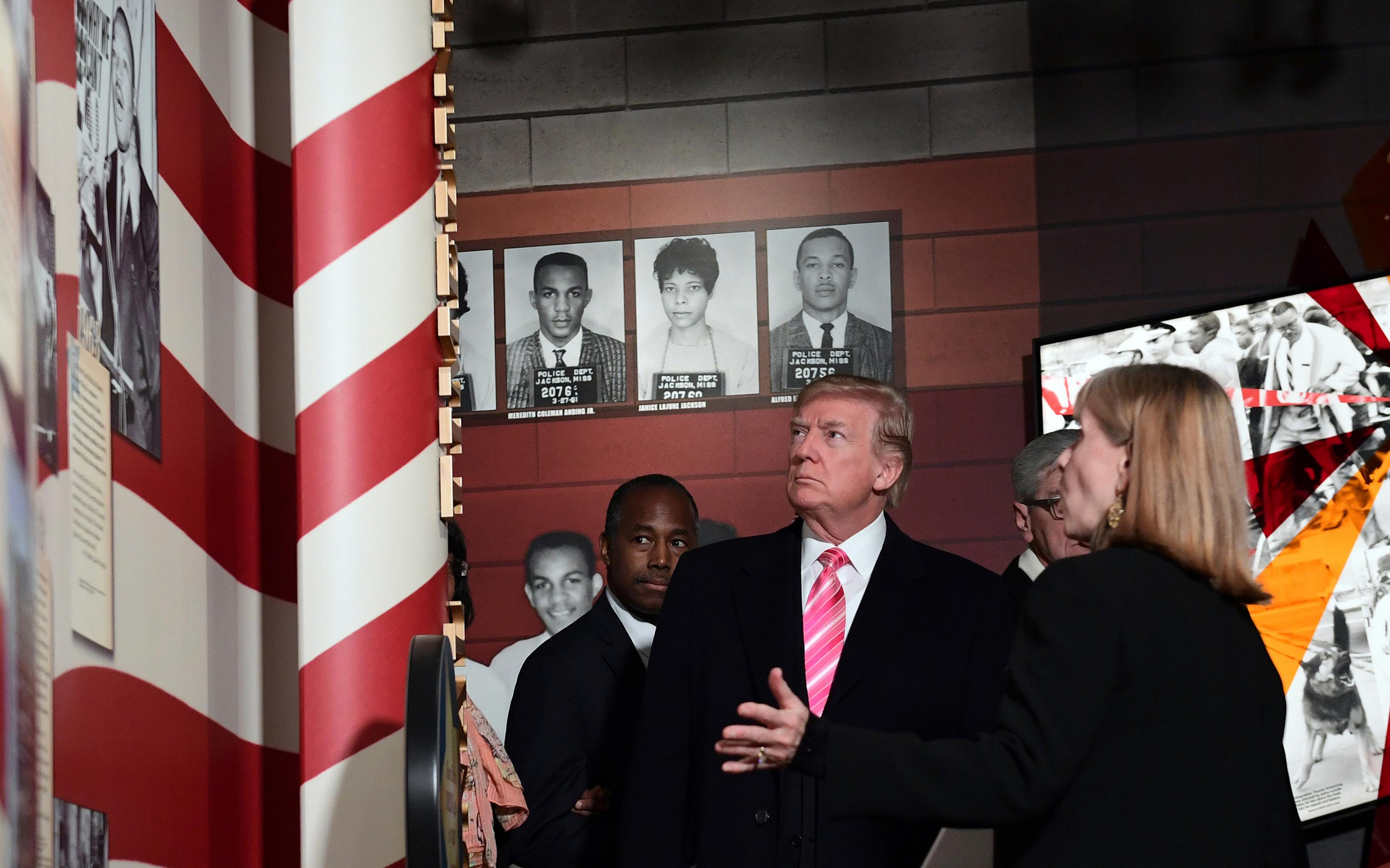 President Donald Trump, center, listens to Museum Division Director Lucy Allen, right, during a tour of the newly opened Mississippi Civil Rights Museum in Jackson, Miss., Saturday, Dec. 9, 2017. Housing and Urban Development Secretary Ben Carson, left, joins the president on the tour. (AP Photo/Susan Walsh)