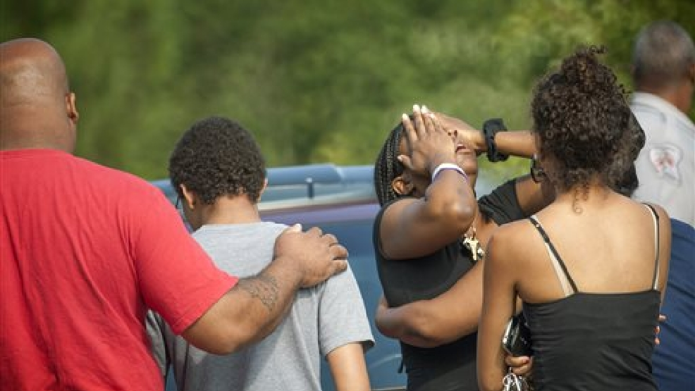 People comfort each other after a shooting in Fayetteville, N.C., Wednesday, July 30, 2014. A domestic dispute erupted into a gun battle with deputies Wednesday at a North Carolina mobile home park, leaving three people dead and three officers wounded, officials said. (AP Photo/The Fayetteville Observer, Cindy Burnham)