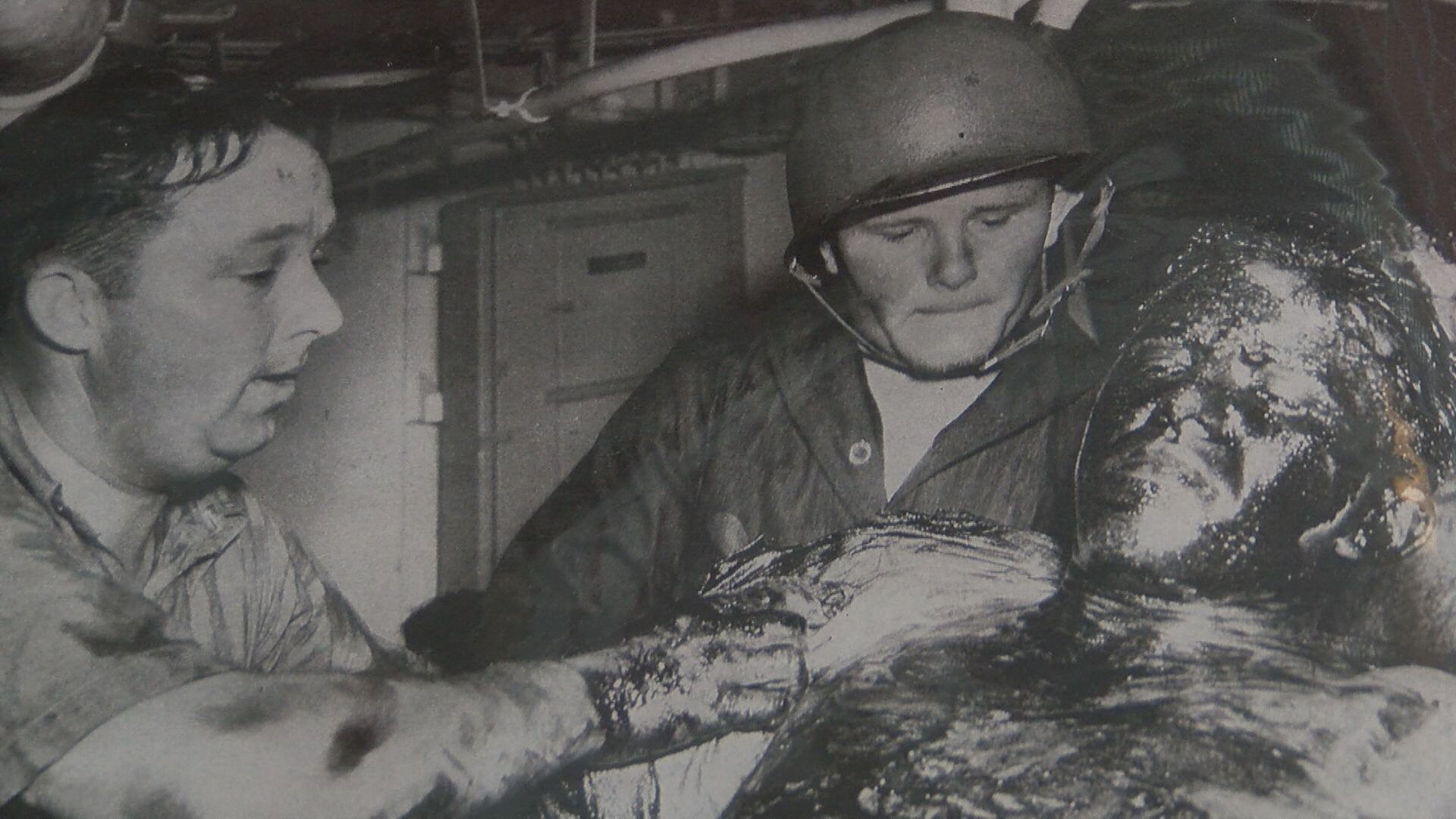 A photo of servicemen caring for one of the survivors, who is covered in oil from the ship. (Thomas Gray/WCYB)