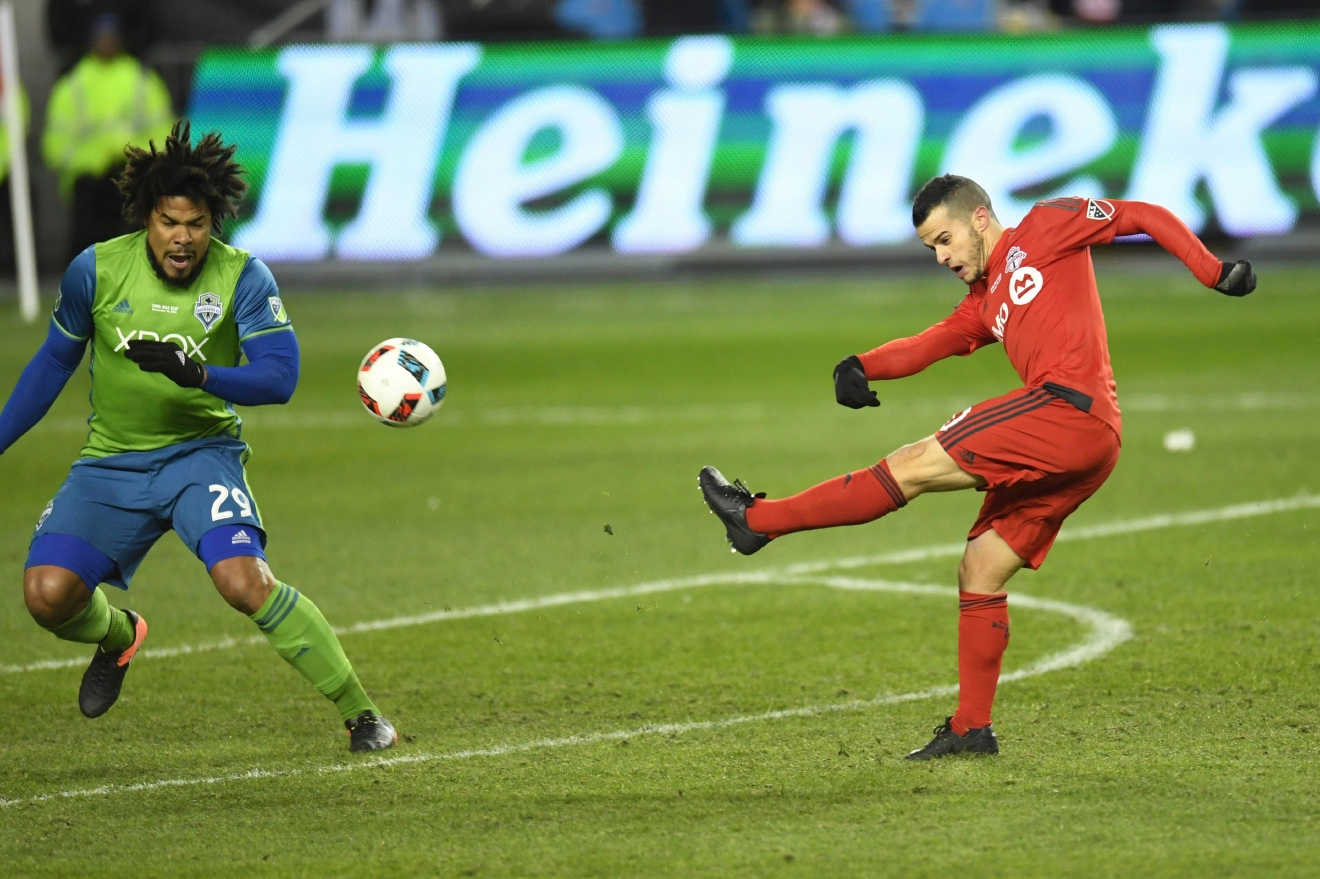 Toronto FC forward Sebastian Giovinco (10) hits Seattle Sounders defender Roman Torres (29) in the face as he shoots on net during first-half MLS Cup final soccer action in Toronto, Saturday, Dec. 10, 2016. (Frank Gunn/The Canadian Press via AP)