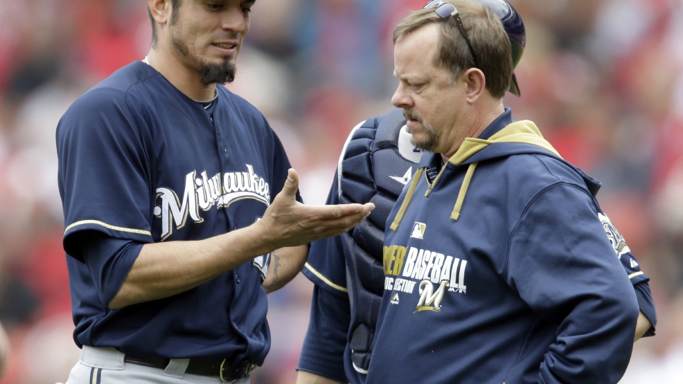 Milwaukee Brewers starting pitcher Matt Garza, left, shows his hand to trainer Dan Wright during the fourth inning of a baseball game against the St. Louis Cardinals Wednesday, April 30, 2014, in St. Louis. Garza left the game due to an injury. (AP Photo/Jeff Roberson)