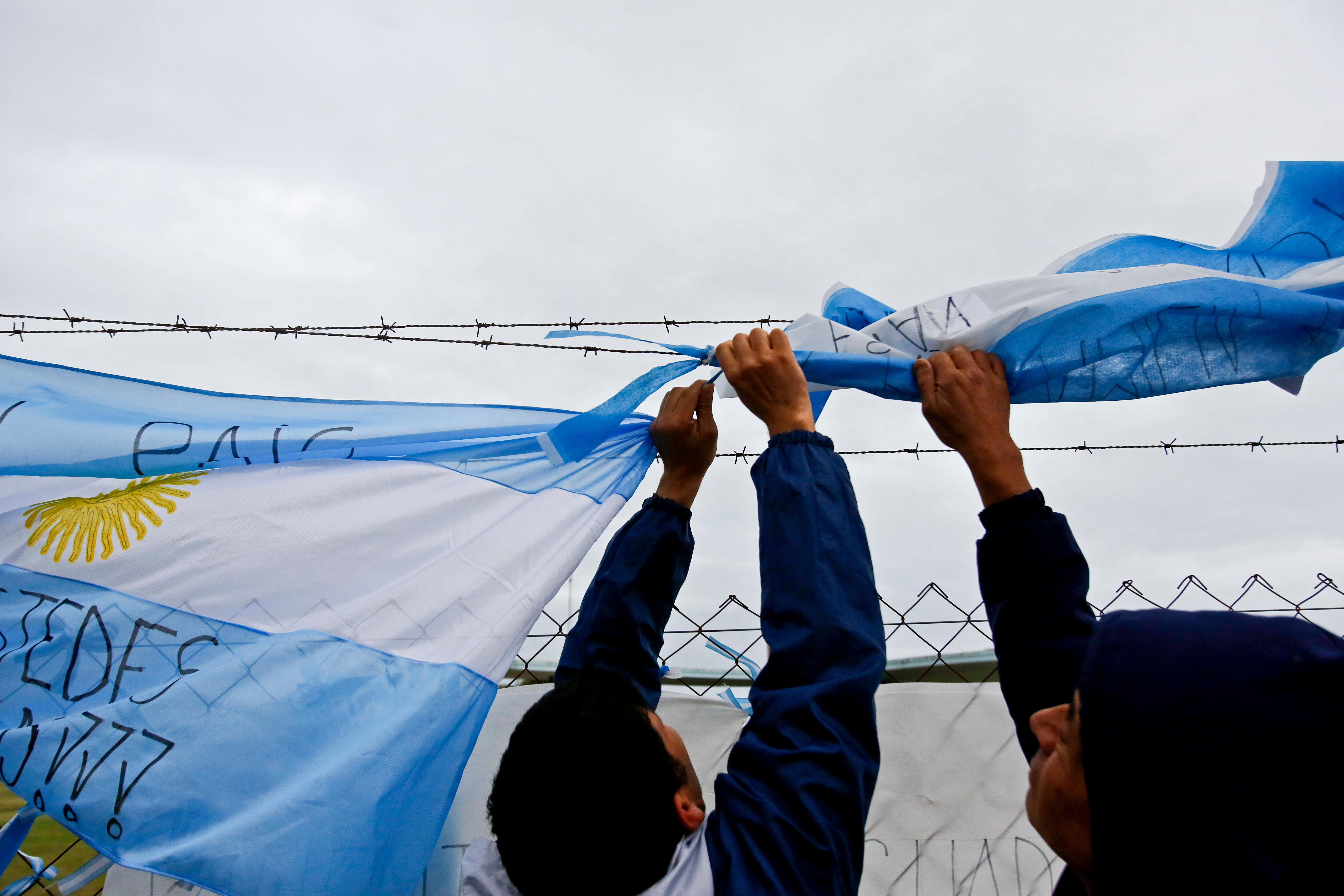 Men hang an Argentine flag on a fence at the Mar de Plata Naval Base after the navy announced a sound detected during the search for the missing ARA San Juan submarine is consistent with that of an explosion, in Mar de Plata, Argentina, Thursday, Nov. 23, 2017. A Navy spokesperson said the search will continue until there is full certainty about the fate of the submarine, adding there was no sign the explosion might be linked to any attack. (AP Photo/Esteban Felix)