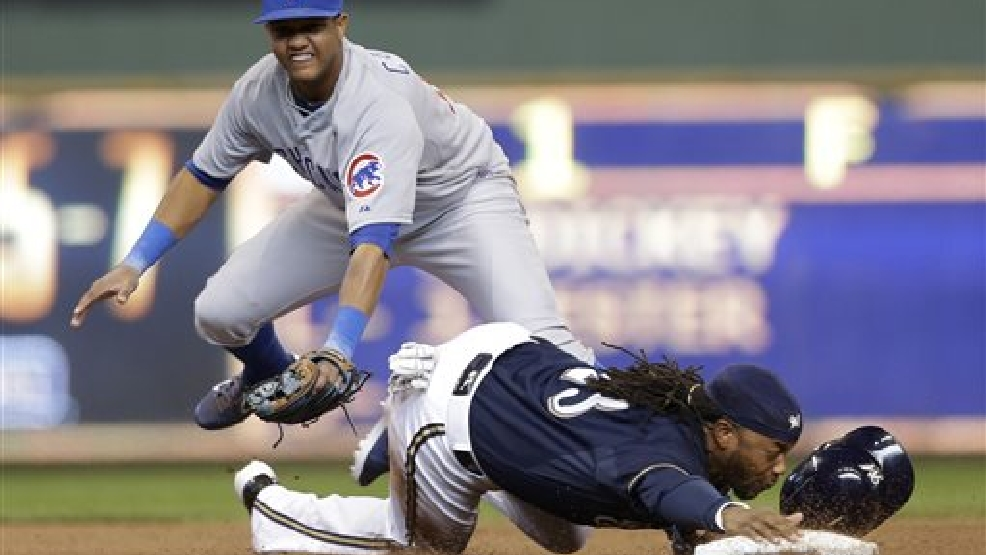 Chicago Cubs' Starlin Castro, left, forces out Milwaukee Brewers' Rickie Weeks at second base and throws to first for a double play on Brewers' Scooter Gennett during the eighth inning of a baseball game on Sunday, April 27, 2014, in Milwaukee. (AP Photo/Jeffrey Phelps)