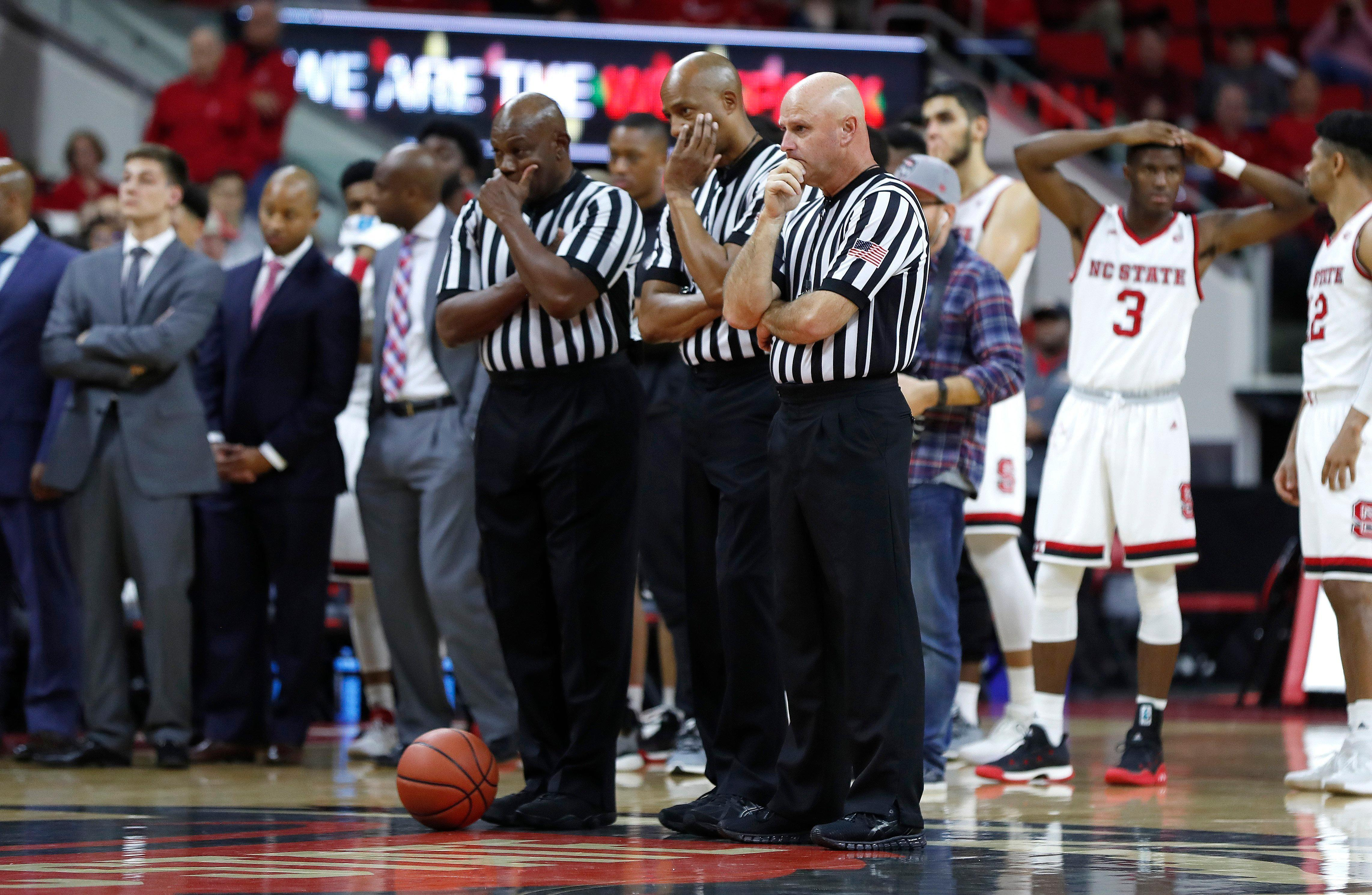 Game 0fficials including from left, Les Jones, Bert Smith and Tim Comer, watch as South Carolina State's Tyvoris Solomon is attended to after he was injured during the first half of an NCAA college basketball game against North Carolina State at PNC Arena in Raleigh, N.C., Saturday, Dec. 2, 2017.  (Ethan Hyman/The News & Observer via AP)