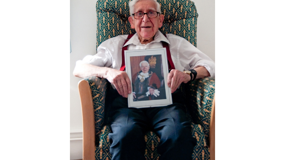 This undated handout image issued by Gracewell Healthcare on Friday, June 6, 2014, of Bernard Jordan an 89-year-old veteran, holding a picture of himself as the Mayor of Hove from 1995 to 1996. (AP Photo/Gracewell Healthcare/PA)