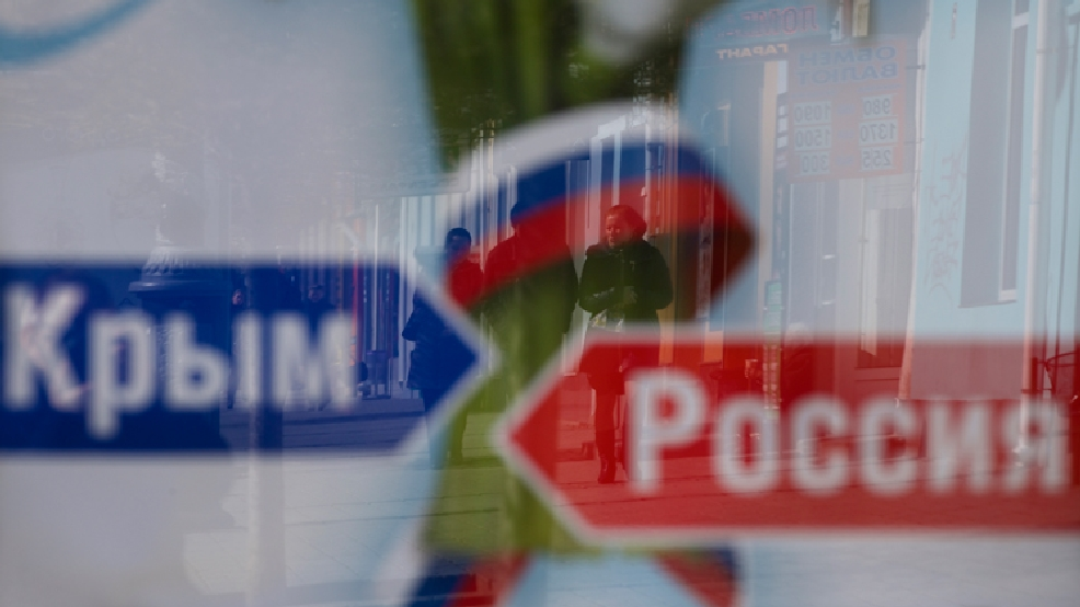 A couple's image reflected on an advertising board reading 'Russia, Crimea', on a street in Simferopol, Ukraine, on Monday, March 17, 2014. Ukraine's Crimean peninsula declared itself independent Monday after its residents voted overwhelmingly to secede and join Russia, while the United States and the European Union slapped sanctions against some of those who promoted the divisive referendum. (AP Photo/Ivan Sekretarev)