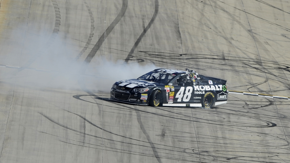 Jimmie Johnson celebrates with a burnout after he won the NASCAR Sprint Cup series auto race, Sunday, June 1, 2014, at Dover International Speedway in Dover, Del. (AP Photo/Nick Wass)