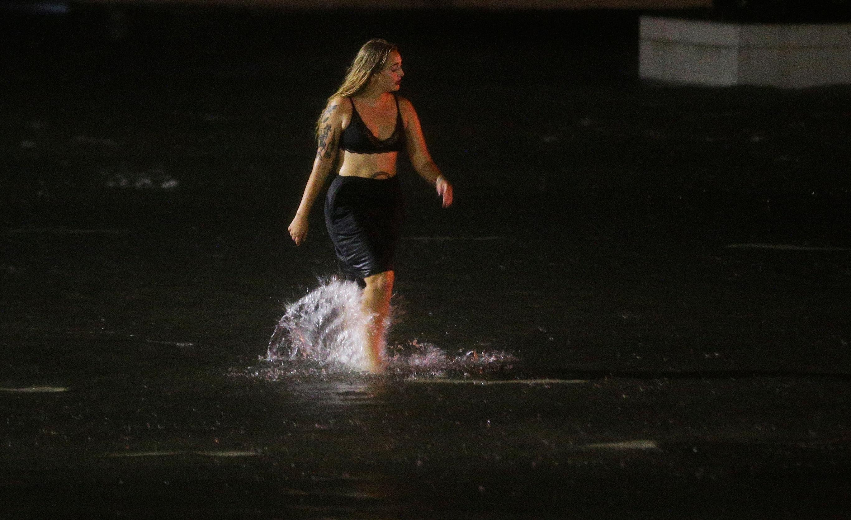 A woman wades through a flooded Water St. in downtown Mobile, Ala., during Hurricane Nate, Sunday, Oct. 8, 2017, in Mobile, Ala. (AP Photo/Brynn Anderson)