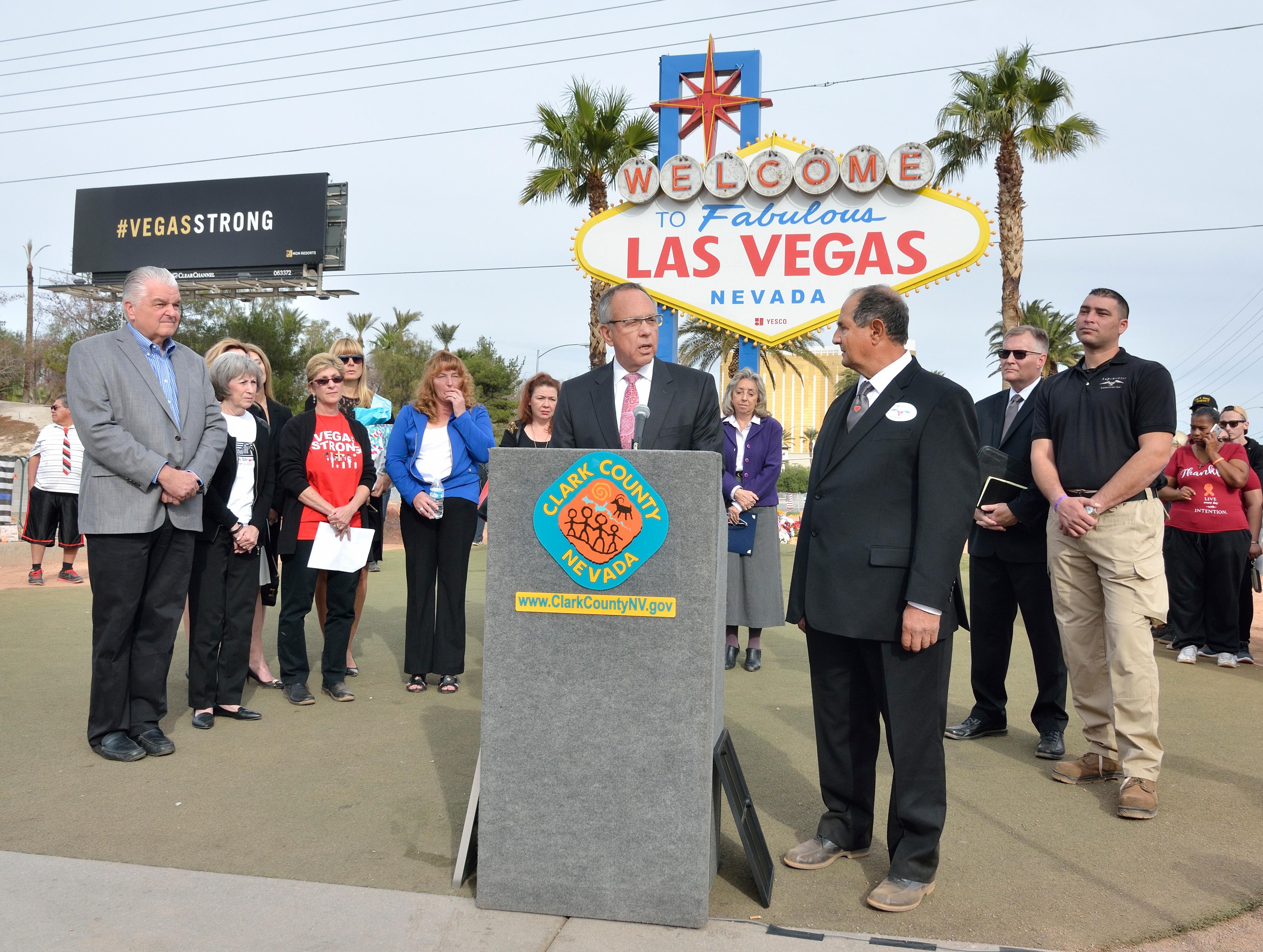 "Clark County Commissioner Jim Gibson, at podium, speaks as Greg Zanis listens during ""Greg Zanis Day"" at the Welcome to Fabulous Las Vegas sign on the Las Vegas Strip on Sunday, Nov. 12, 2017. Zanis, a carpenter from Aurora, Ill., was recognized by the Clark County Commision for creating 58 crosses memorializing those who died during the Route 91 Harvest festival shooting on Oct. 1. The crosses were later moved to the Clark County Museum for its permanent collection. [Bill Hughes/Las Vegas News Bureau]"