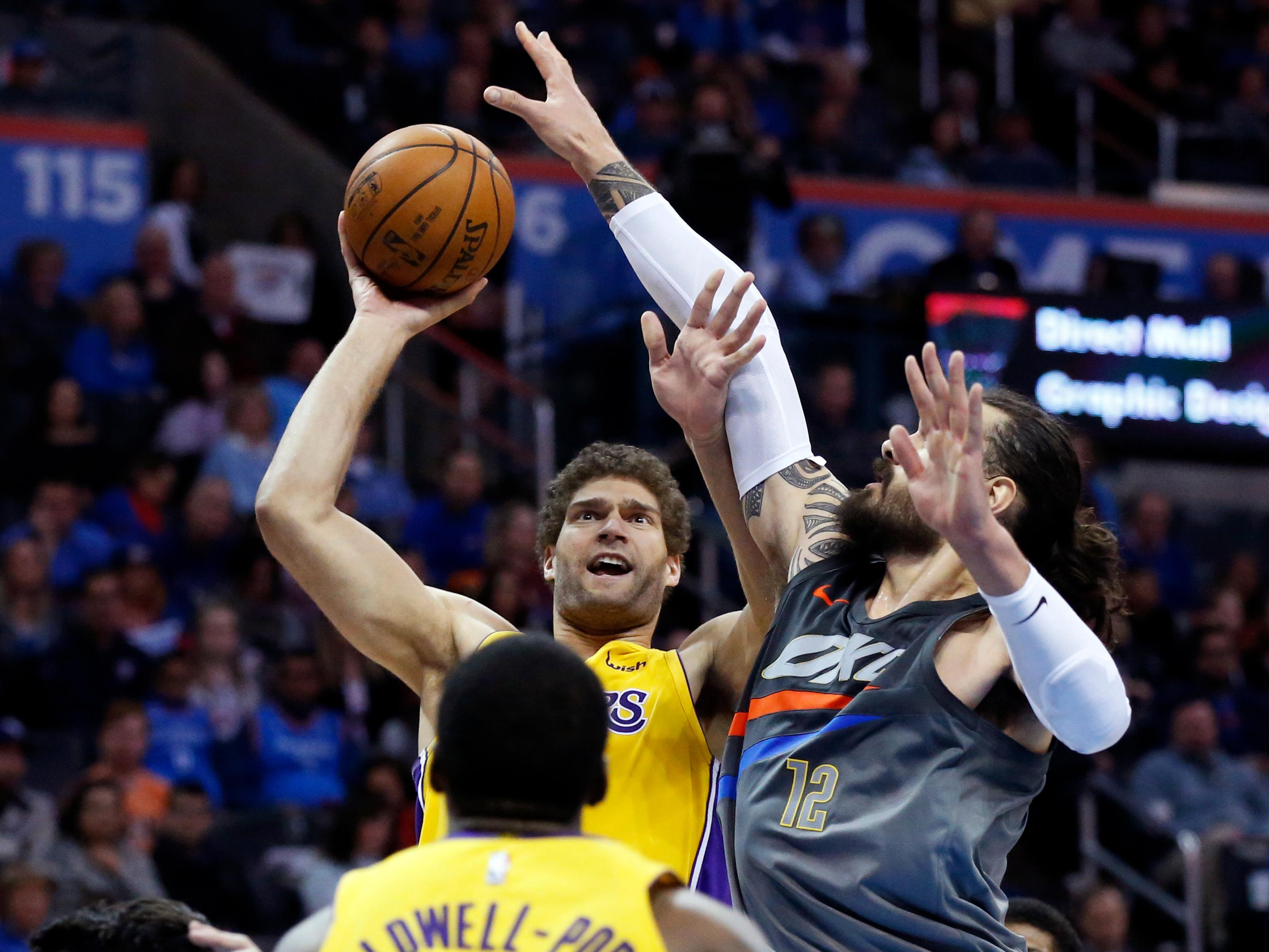 Los Angeles Lakers center Brook Lopez, top left, shoots in front of Oklahoma City Thunder center Steven Adams (12) in the first half of an NBA basketball game in Oklahoma City, Sunday, Feb. 4, 2018. (AP Photo/Sue Ogrocki)