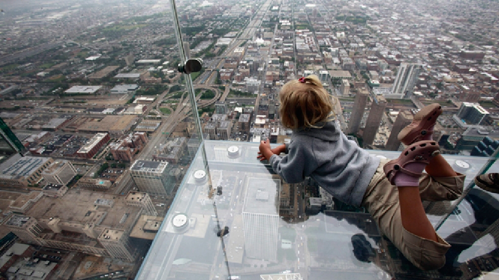 "FILE - This June 24, 2009 file photo shows Anna Kane, 5, looking down from the ""The Ledge,"" at Chicago's Willis Tower. Officials at the building say the popular tourist attraction is safe, even though the glass ledge jutting from the building's 103rd floor appeared to crack Wednesday, May 28, 2014, beneath the feet of a visiting family. The see-through glass bays extend about four feet from the building, which was once called the Sears Tower. (AP Photo/Kiichiro Sato, File)"