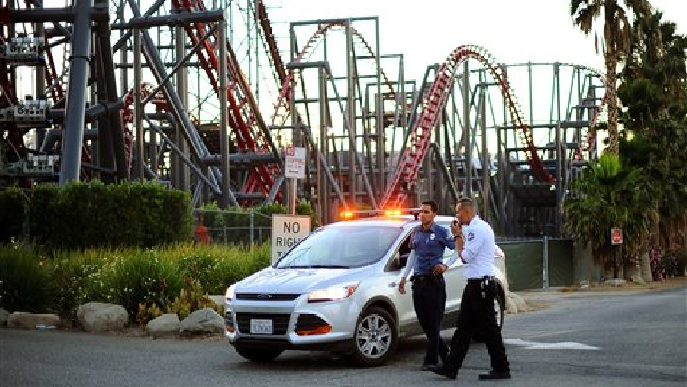 Members of the Six Flags Magic Mountain amusement park security staff monitor the situation at the exit of the park after riders were injured on the Ninja coaster, not shown, Monday, July 7, 2014, in Valencia, Calif.  (AP Photo/Los Angeles Daily News, Andy Holzman)