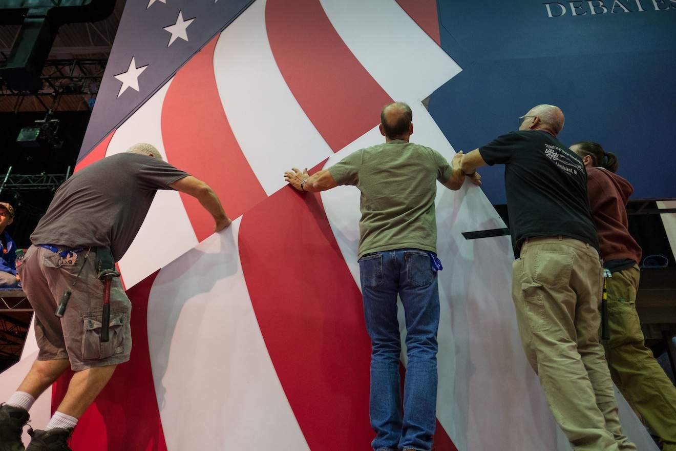 Construction crews hang part of the set as preparations continue for the Monday Sept. 26, 2016, presidential debate between Democratic Hillary Clinton and Republican candidate Donald Trump, Saturday, Sept. 24, 2016, at Hofstra University in Hempstead, N.Y. (AP Photo/J. David Ake)