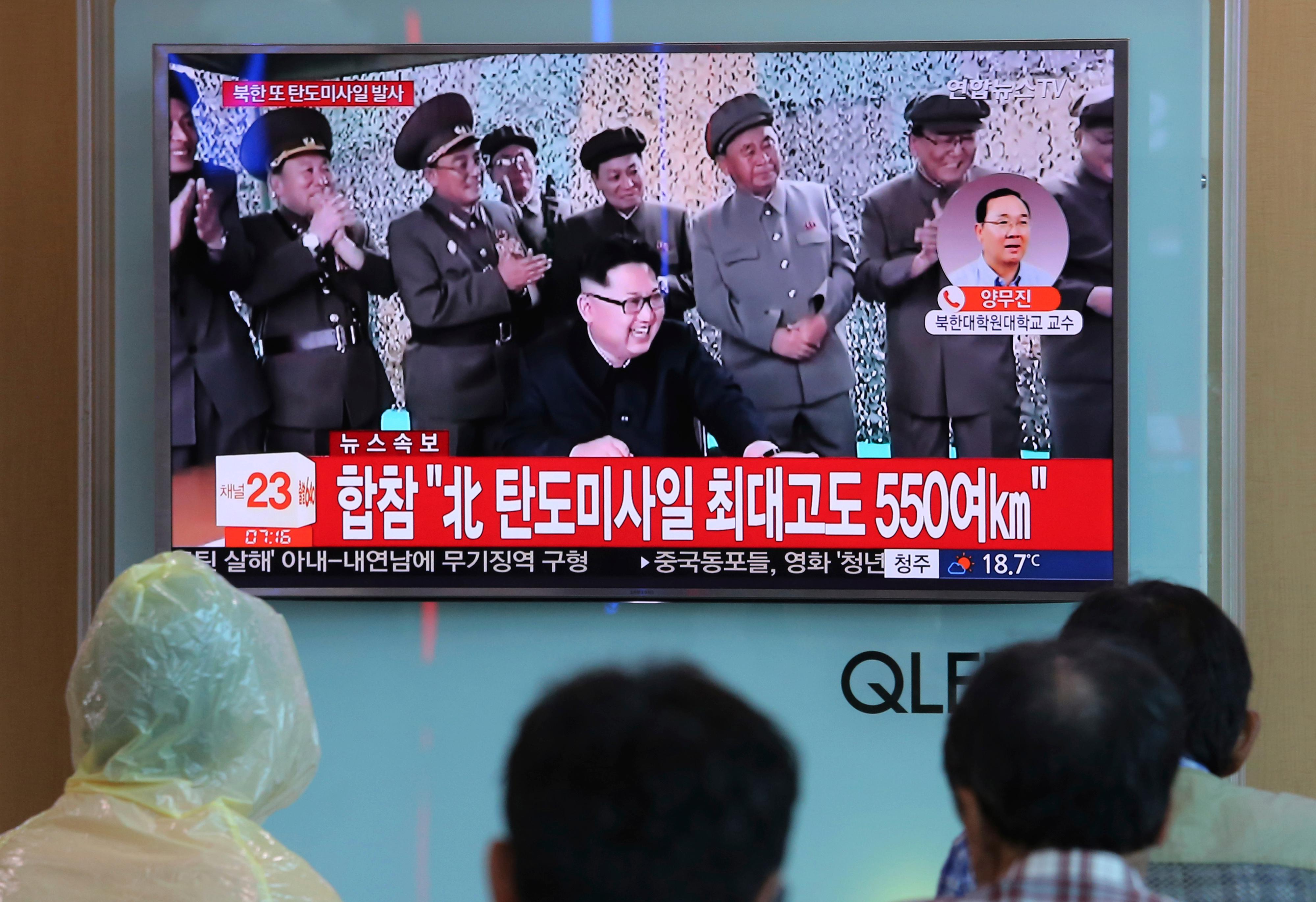"People watch a TV screen showing a file image of North Korean leader Kim Jong Un, bottom center, at the Seoul Railway Station in Seoul, South Korea, Tuesday, Aug. 29, 2017. The signs read ""North Korean missile flies with height of 550 km."" (AP Photo/Ahn Young-joon)"