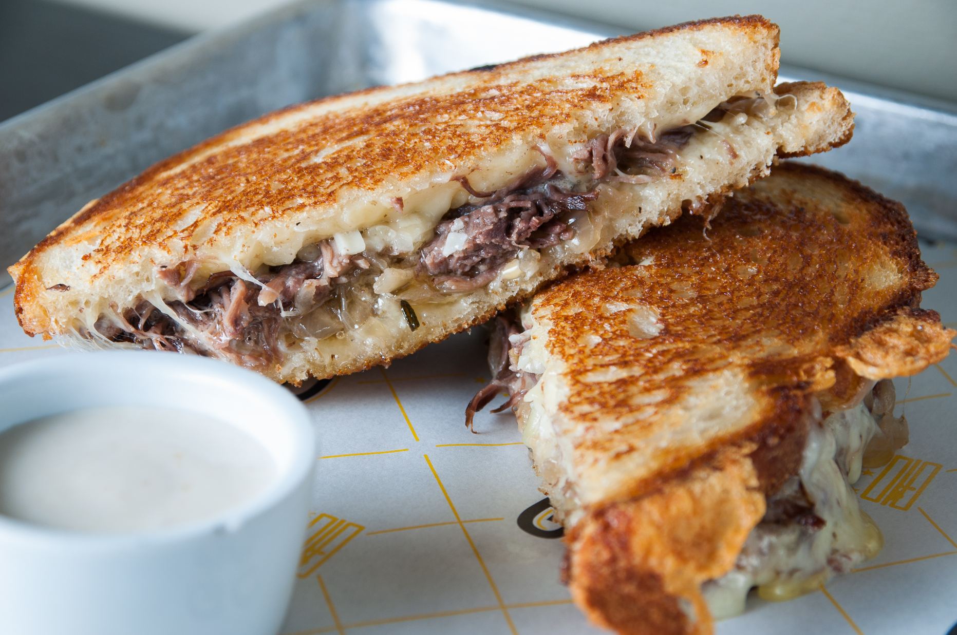 Sourdough gets packed with Gruyere, blue cheese, slow cooked short ribs, and caramelized onions. The rich 'wich arrives with a side of horseradish dip to cut super savoriness. (Image: Courtesy GCDC)