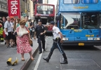 A woman, her arm bandaged and in a sling, leaves after being treated at the scene of a traffic accident apparently involving two double-decker tour buses in New York's Times Square, Tuesday Aug. 5, 2014. The Fire Department of New York says 11 people suffered injuries, three of them seriously, but none of the injuries is believed to be life-threatening. (AP Photo/Bebeto Matthews)