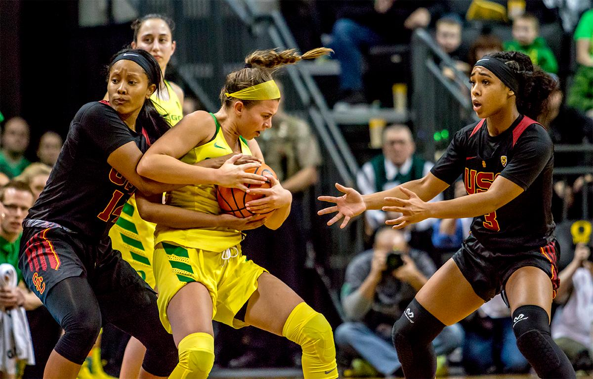 The Duck's Lexi Bando (#10) is grabbed from behind by the Trojan's Sadie Edwards (#14). The Oregon Ducks defeated the USC Trojans 80-74 on Friday at Matthew Knight Arena in a  game that went into double overtime. Lexi Bando sealed the Ducks victory by scoring a three-pointer in the closing of the game. Ruthy Hebard set a new NCAA record of 30 consecutive field goals, the old record being 28. Ruthy Hebard got a double-double with 27 points and 10 rebounds, Mallory McGwire also had 10 rebounds. The ducks had four players in double digits. The Ducks are now 24-4, 13-2 in the Pac-12, and are tied for first with Stanford. Photo by August Frank, Oregon News Lab