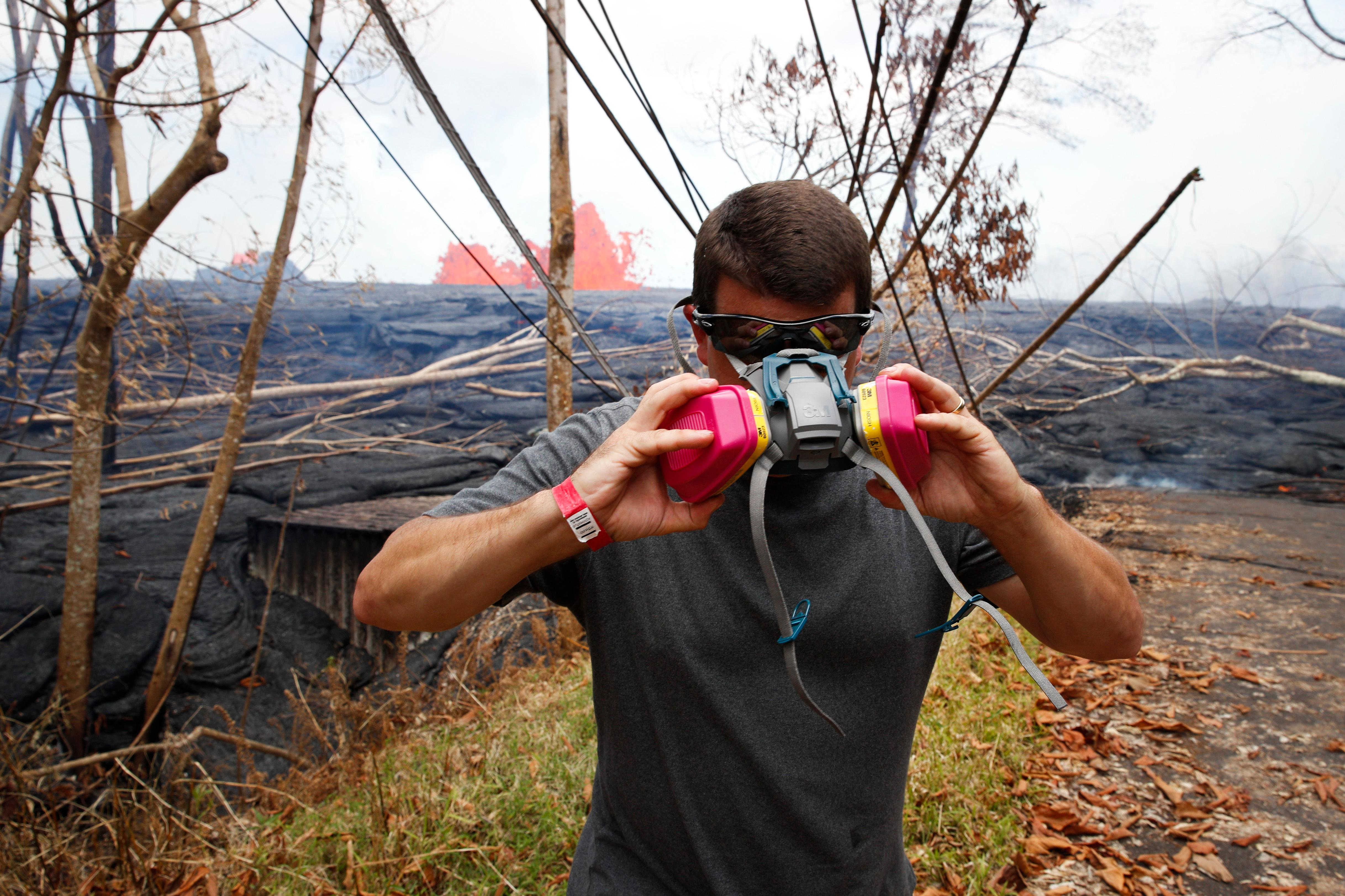 Heath Dalton removes his mask as lava erupts from fissures in the Leilani Estates subdivision near Pahoa, Hawaii, Tuesday, May 22, 2018. Authorities were racing Tuesday to close off production wells at a geothermal plant threatened by a lava flow from Kilauea volcano on Hawaii's Big Island. (AP Photo/Jae C. Hong)