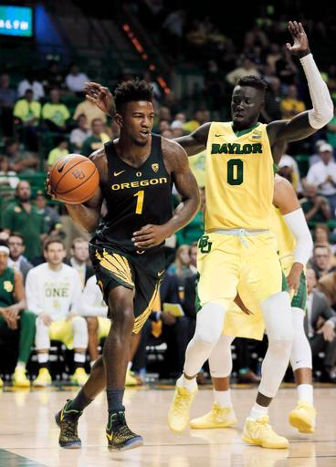 Oregon forward Jordan Bell (1) drives the baseline to the basket as Baylor's Jo Lual-Acuil Jr. (0) of Australia defends in the first half of an NCAA college basketball game, Tuesday Nov. 15, 2016, in Waco, Texas. (AP Photo/Tony Gutierrez)