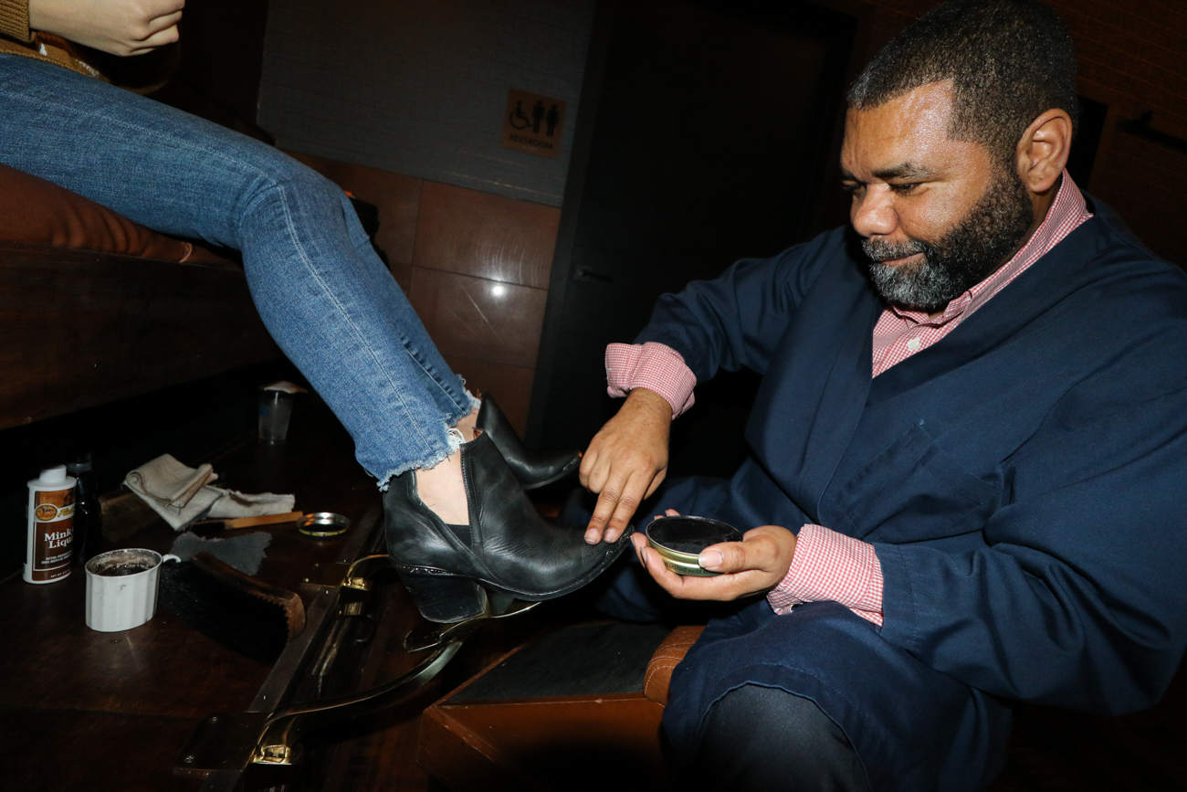 Damien Watkins of Finneytown provides a customer with a shoe shine. The complimentary service is available on Wednesdays between 4 and 7 PM. / Image: Ronny Salerno // Published: 1.2.19