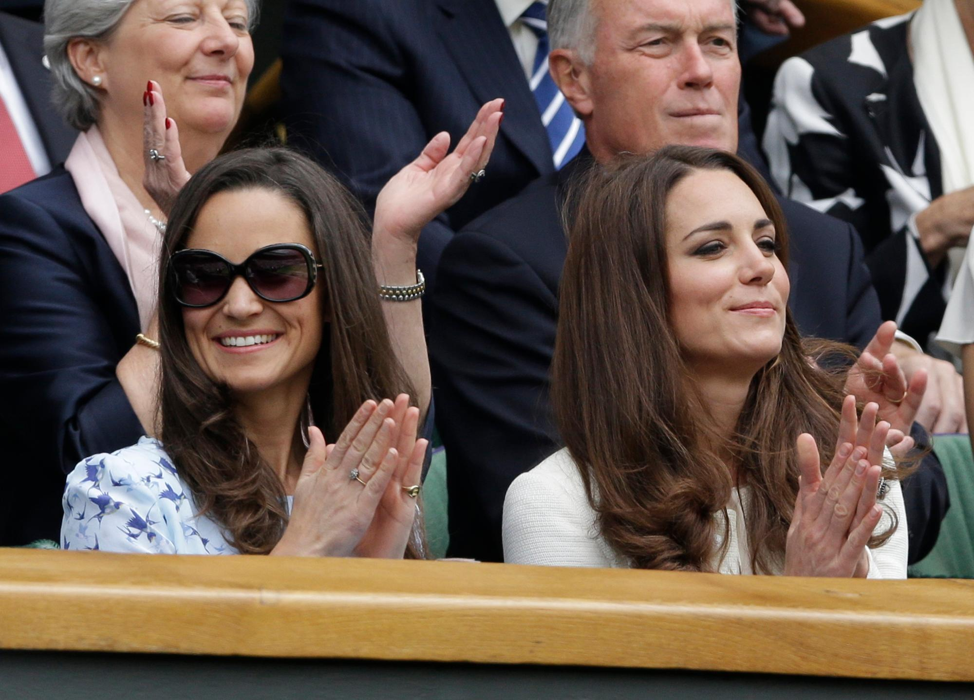 FILE - In this Sunday, July 8, 2012 file photo, Kate, Duchess of Cambridge, right, and her sister Pippa Middleton, left, applaud before the start of the men's singles final between Roger Federer of Switzerland and Andy Murray of Britain at the All England Lawn Tennis Championships at Wimbledon, England. 33-year-old Pippa Middleton is marrying a wealthy financier in the village of Englefield, west of London on Saturday May 20, 2017, with a guest list of young A-list royals and reality TV stars looking on. (AP Photo/Kirsty Wigglesworth, File)