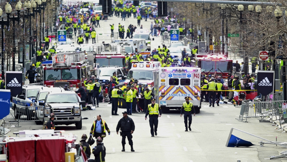 Police clear the area at the finish line of the 2013 Boston Marathon as medical workers help injured following explosions in Boston, Monday, April 15, 2013. (AP Photo/Charles Krupa)