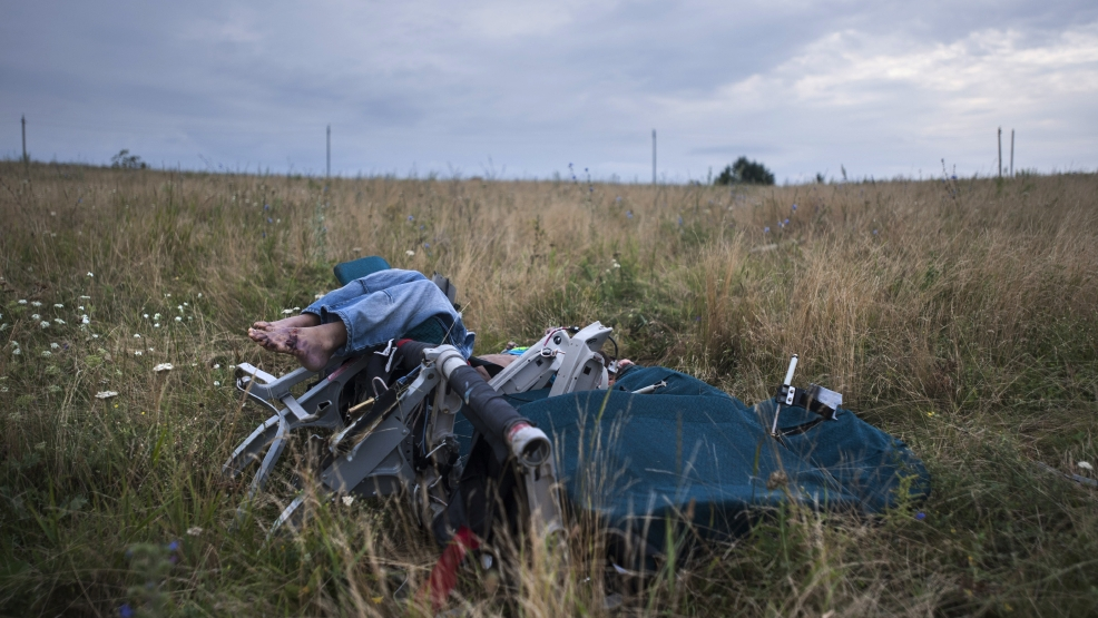 CAPTION CORRECTION, CORRECTS TO IMPROVE SYNTAX AND CLARITY OF CAPTION - The body of a passenger is partially visible as it lies in a chair at the crash site of Malaysia Airlines Flight 17 near the village of Hrabove, eastern Ukraine, Saturday, July 19, 2014. World leaders demanded Friday that pro-Russia rebels who control the eastern Ukraine crash site of Malaysia Airlines Flight 17 give immediate, unfettered access to independent investigators to determine who shot down the plane. (AP Photo/Evgeniy Maloletka)
