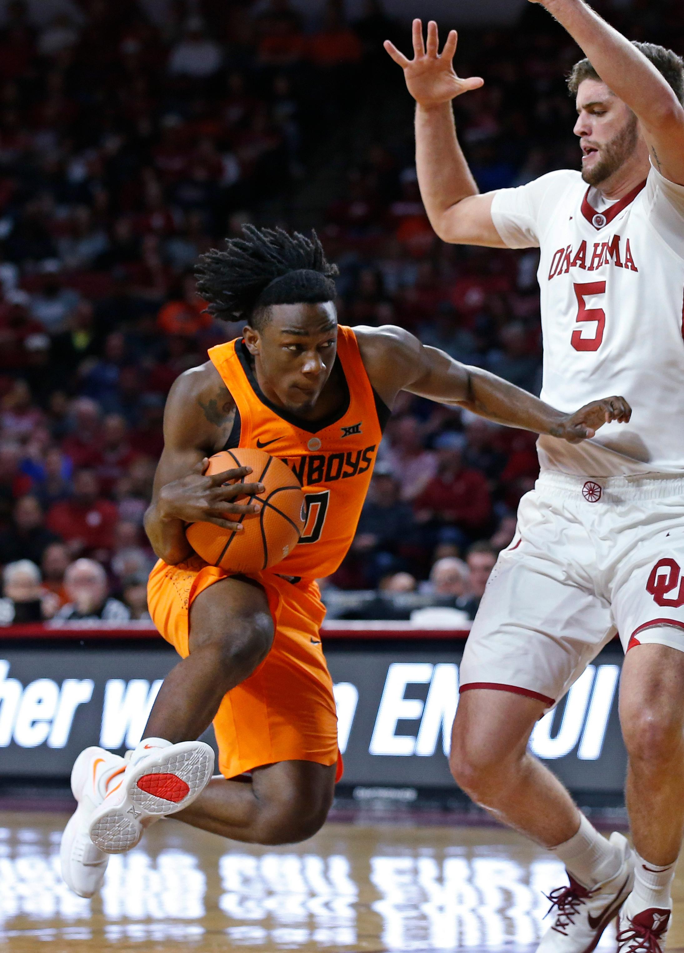Oklahoma State guard Brandon Averette (0) drives around Oklahoma forward Matt Freeman (5) during the first half of an NCAA college basketball game in Norman, Okla., Wednesday, Jan. 3, 2018. (AP Photo/Sue Ogrocki)