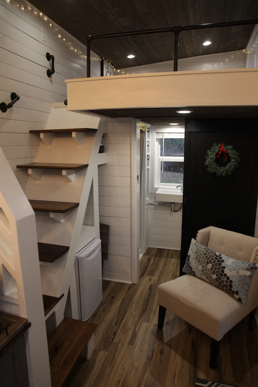The stairs leading to the loft in the Trillium tiny house with the refrigerator below and a small closet space to the right, just before the door to the bathroom / Image: Chez Chesak{ }// Published: 1.24.21